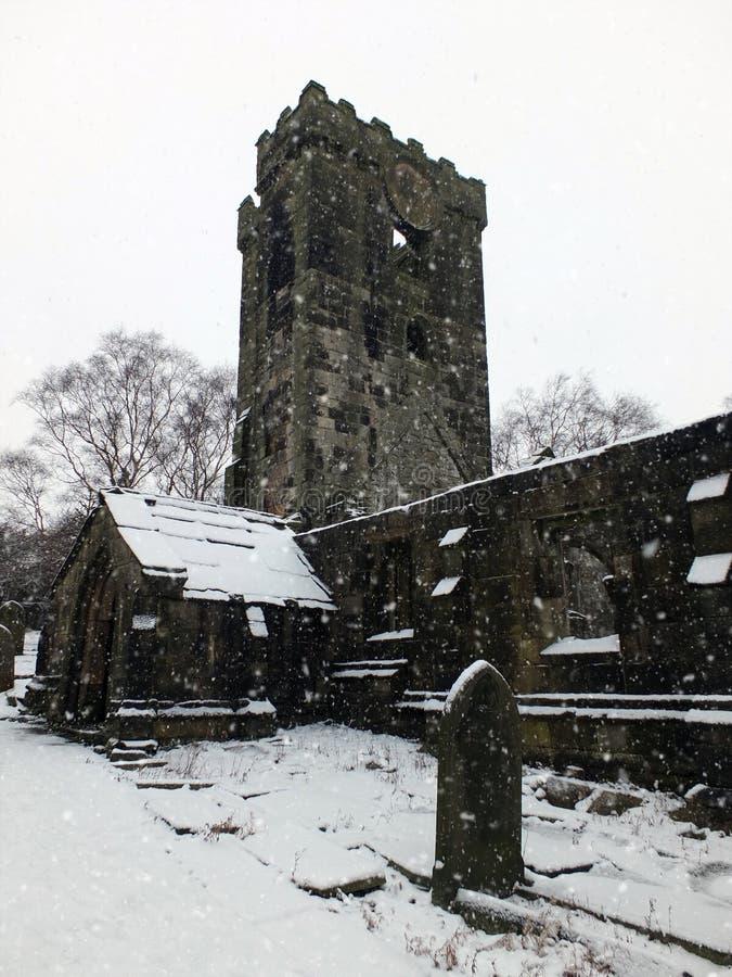 Der Schnee auf ruinierter mittelalterlicher Kirche im heptonstall mit Friedhof lizenzfreie stockfotografie