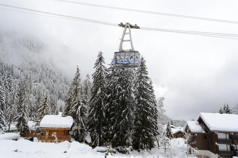 Der schneebedeckte Wald und die alpinen Chalets an einer Drahtseilbahn lizenzfreie stockbilder