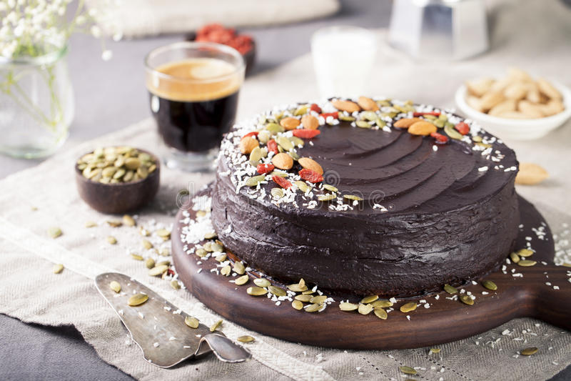 Der Schokoladen-roten Rübe des strengen Vegetariers Kuchen mit der bereifenden Avocado, verzierte Nüsse, Samen stockfotos