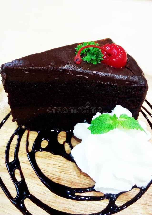 Der Schokoladenkuchen, der mit Schlagsahne und Minze verziert wurde, diente mit heißem Getränk lizenzfreie stockfotos
