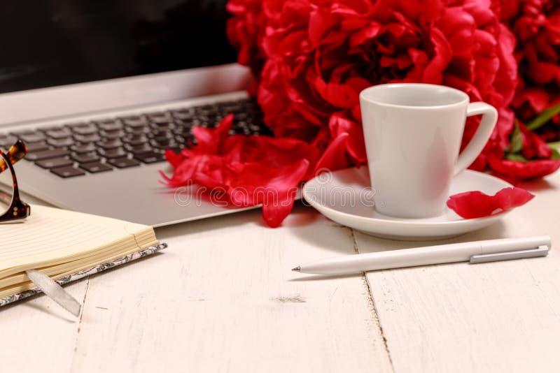 Der Schreibtisch der Ansichtfrauen mit Blumen Weiblicher Arbeitsplatz mit Laptop, Blumenpfingstrosen, Zusätze, Notizbuch, Gläser, lizenzfreies stockfoto