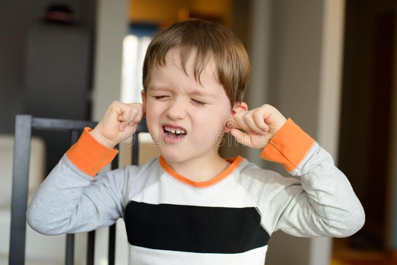 der schreiende Junge mit 4-Jährigen und verstopfen seine Ohren mit den Fingern stockbilder