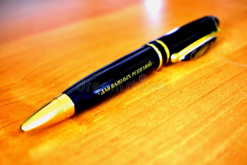 Der schwarze Griff mit einem goldenen Rahmen liegt auf einer Tabelle mit einer Aufschrift für wichtige Entscheidungen Teurer Grif stockfotos