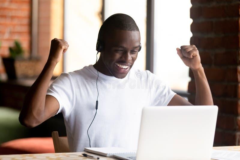 Der schwarze junge Mann, der Bildschirm betrachtet, fühlt sich glücklich stockbilder