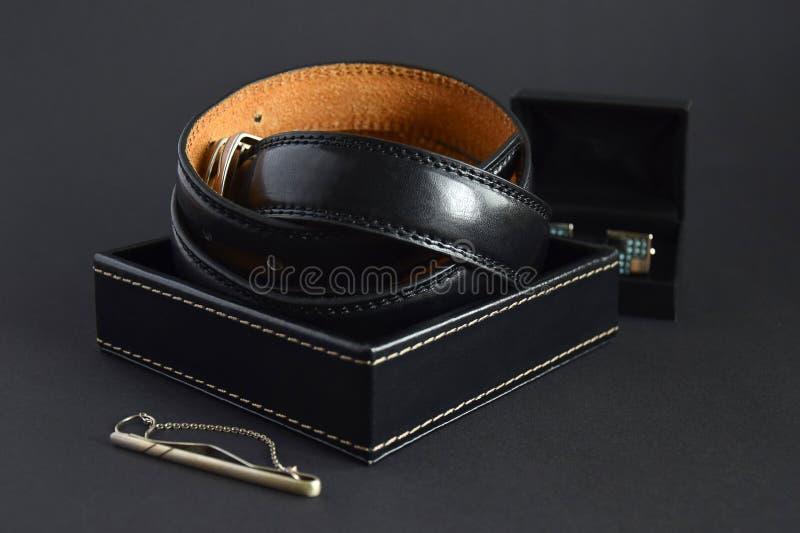 Der schwarze Ledergürtel der Männer im Kasten, im silbernen Krawattenhalter und in den Manschettenknöpfen lizenzfreies stockbild