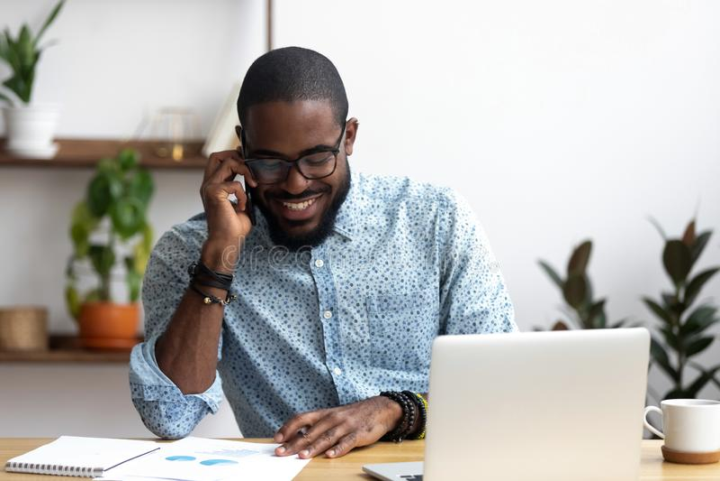 Der schwarze Manager macht Geschäftsanruf sprechend mit Kunden stockfotografie
