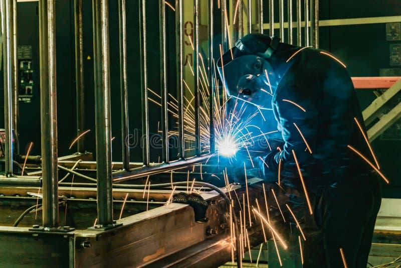 Der Schweißer montiert die Metallbearbeitung im Unternehmen durch verschweißte Verbindungen lizenzfreie stockfotos