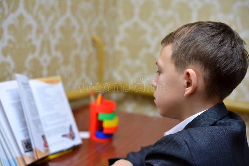 Der selektive Fokus des kleinen Jungen lernend, wie man seinen Namen, Kinderstudie zu Hause, Kinder tun Hausarbeit zu Hause, Konz stockfoto