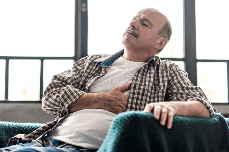Der Senior-Mann hat einen Herzinfarkt Arme Gesundheit im Alter stockbilder