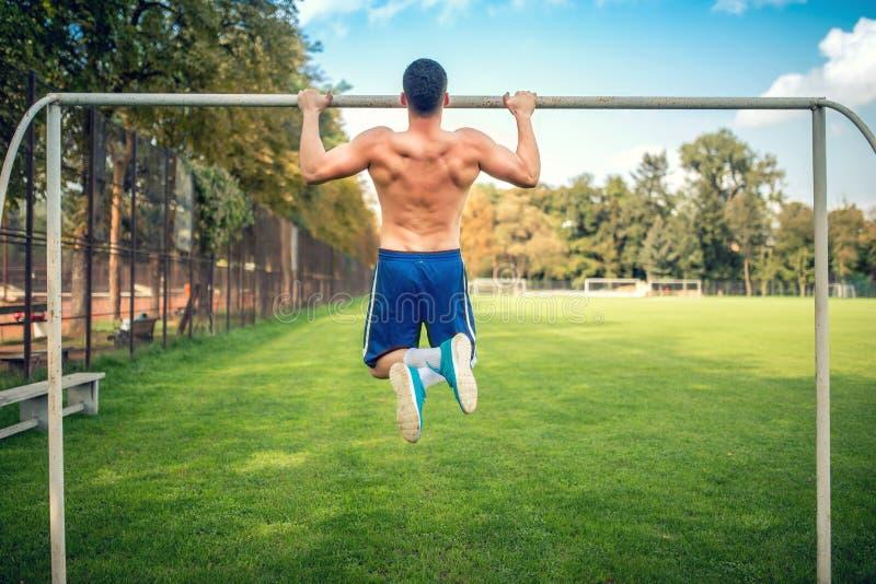 Der sexy Bodybuilder, der im Park, Kinn tuend ausarbeitet, ups und drücken ups Männlicher Eignungsspieler, der draußen ausbildet lizenzfreie stockfotos