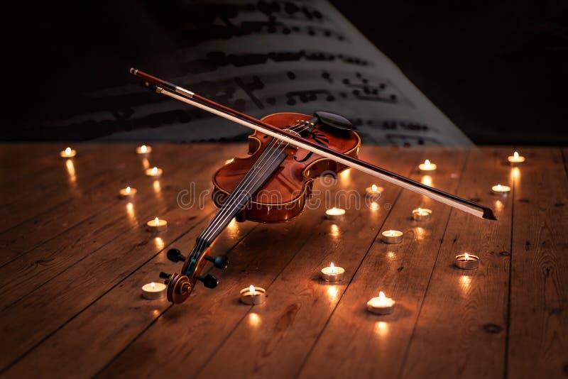 Der sich hin- und herbewegende Geist-Violinen-Lit durch Kerzenlicht stockfoto