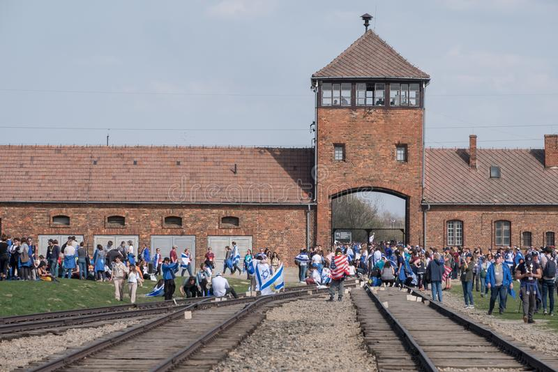 Der Sicherheitsturm am Eingang zu Konzentrationslager Auschwitz Birkenau mit Gruppe Kindern im März des Lebens stockfoto