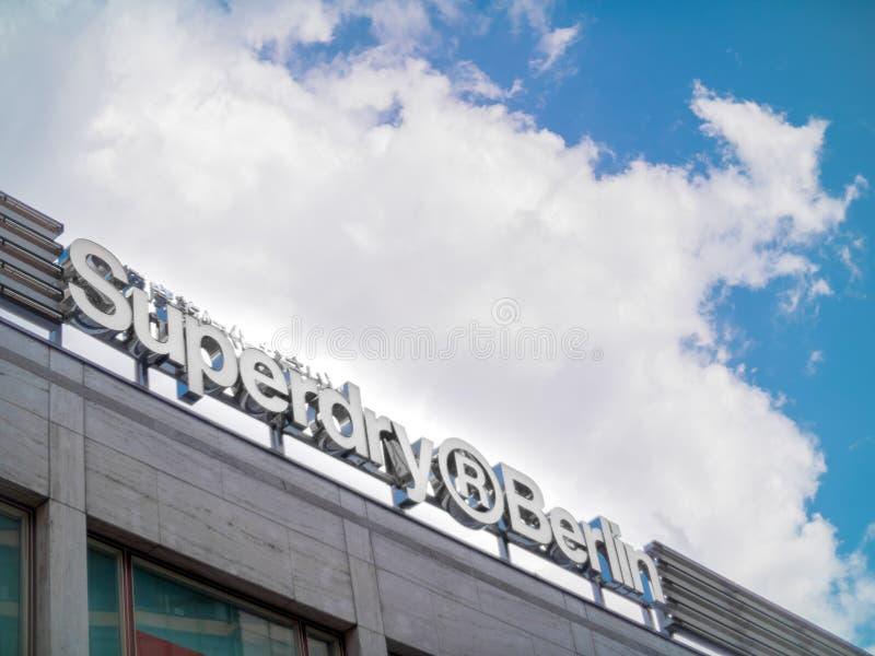 Der Signage für den Superdry-Speicher in Berlin mit großen Wolken lizenzfreie stockfotografie