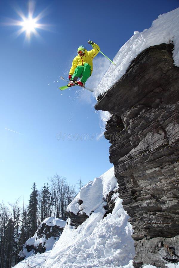Der Skifahrer springend gegen blauen Himmel stockbild