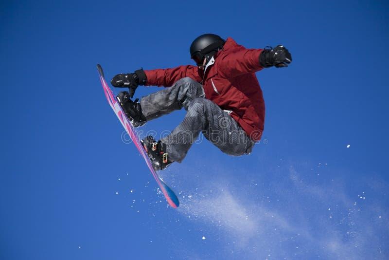 Der Snowboarder hoch springend stockfoto