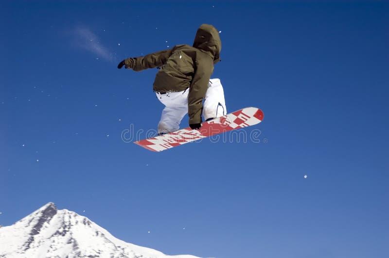 Der Snowboarder hoch springend in die Luft stockbilder