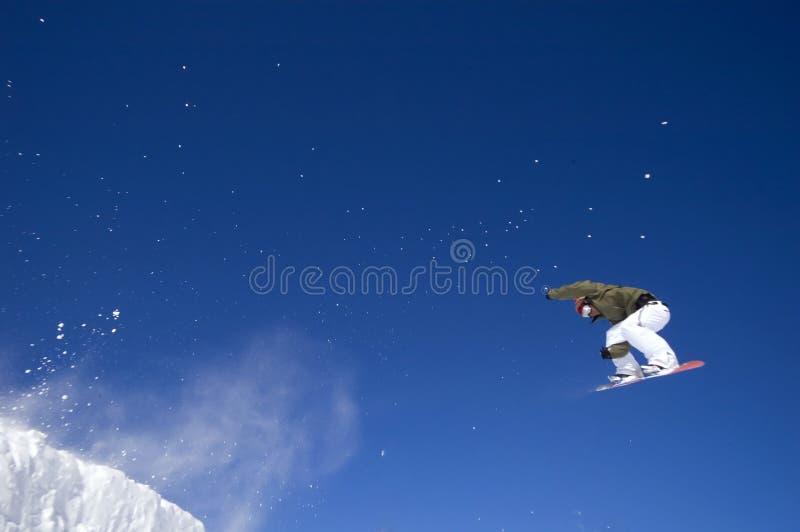 Der Snowboarder hoch springend in die Luft lizenzfreie stockfotografie