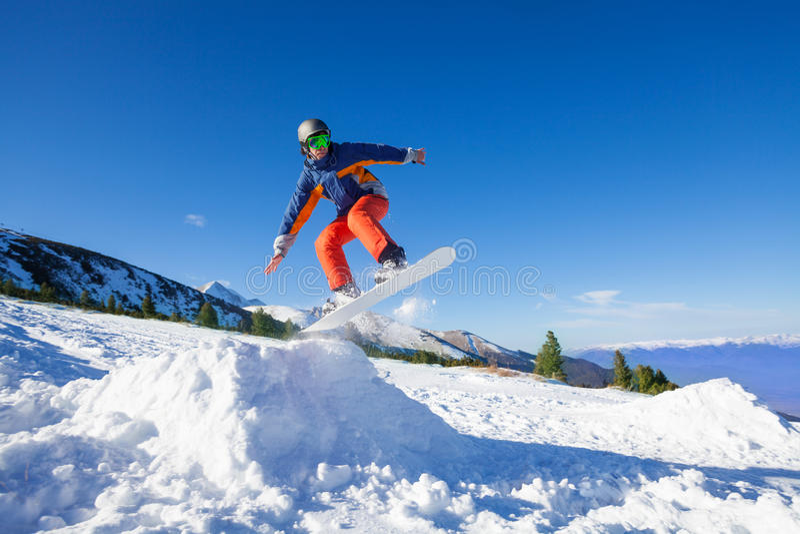 Der Snowboarder hoch springend vom Hügel im Winter stockfoto