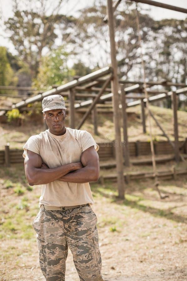 Der Soldat, der mit den Armen steht, kreuzte während des Hindernislaufs im Ausbildungslager lizenzfreies stockbild