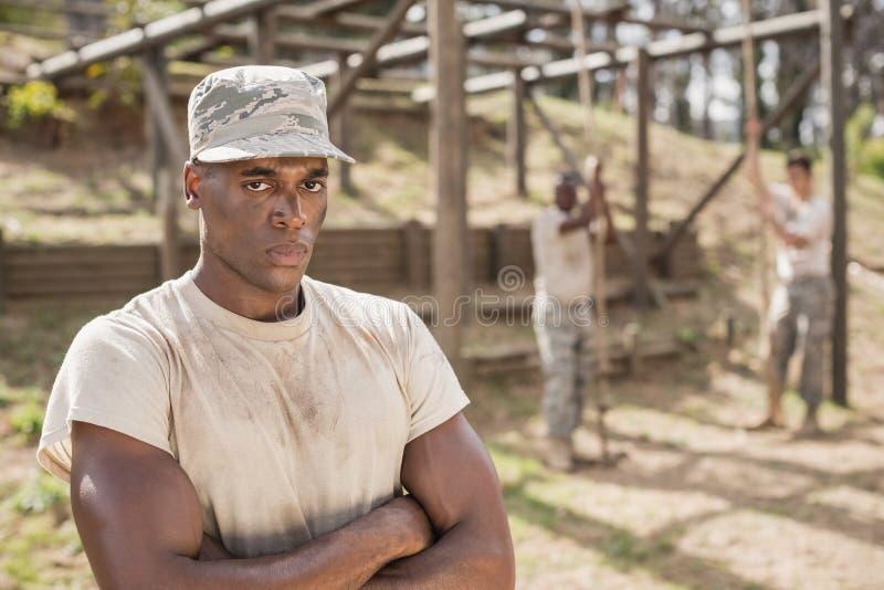 Der Soldat, der mit den Armen steht, kreuzte während des Hindernislaufs im Ausbildungslager lizenzfreie stockfotos