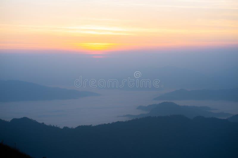 Der Sonnenaufgang am Berg mit dem Nebel und der Bewölkung es stockfotografie