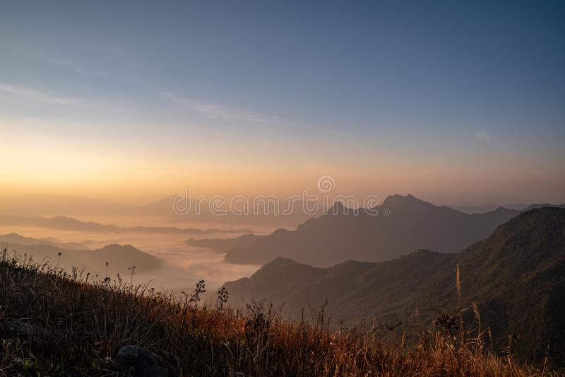 Der Sonnenaufgang am Berg mit dem Nebel und der Bewölkung es lizenzfreie stockfotografie