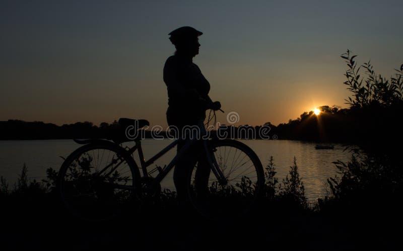 Der Sonnenuntergang über dem See und der Frau mit Fahrrad stockbild