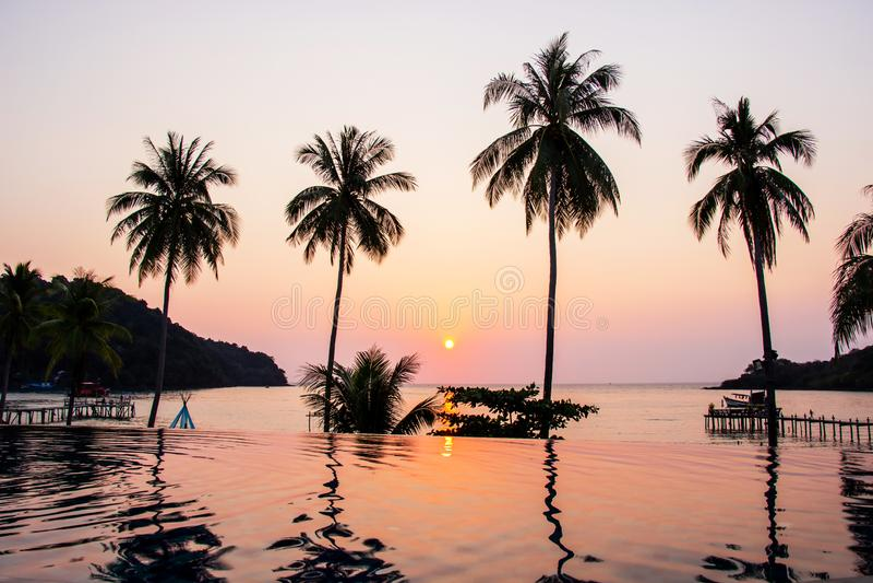Der Sonnenuntergang, der über den Wasseroberflächenvordergrund mit bao Knall des Kokosnussbaum-Bereichs AO in KOH kood Insel nach lizenzfreie stockfotos