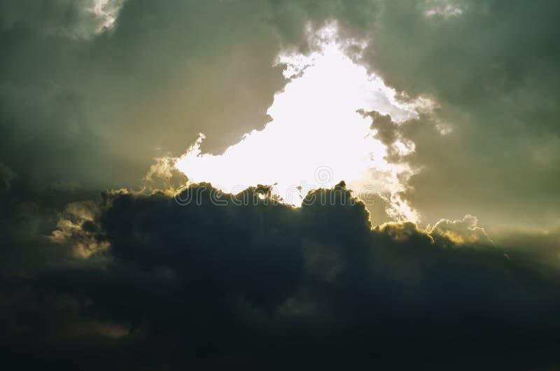 Der Sonnenuntergang-Himmel wird mit Wolken bedeckt Die dunklen starken Wolken und der helle Bruch durch sie lizenzfreie stockbilder