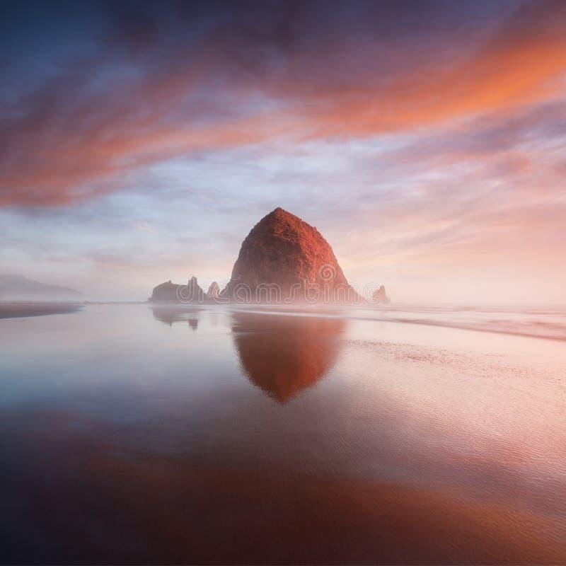 Der Sonnenuntergang am Kanonen-Strand mit drastischen Wolken im Hintergrund und in einer netten Reflexion im Wasser Drastischer K lizenzfreie stockfotos