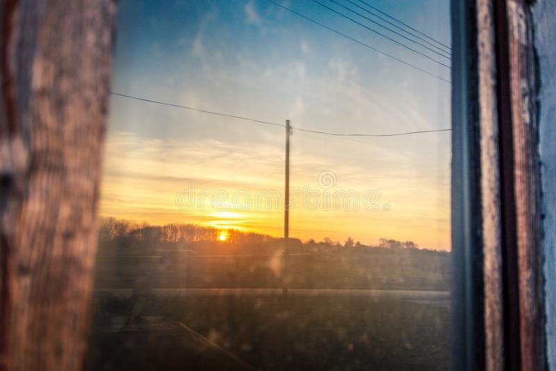 Der Sonnenuntergang wird im alten Hausfenster reflektiert lizenzfreies stockbild