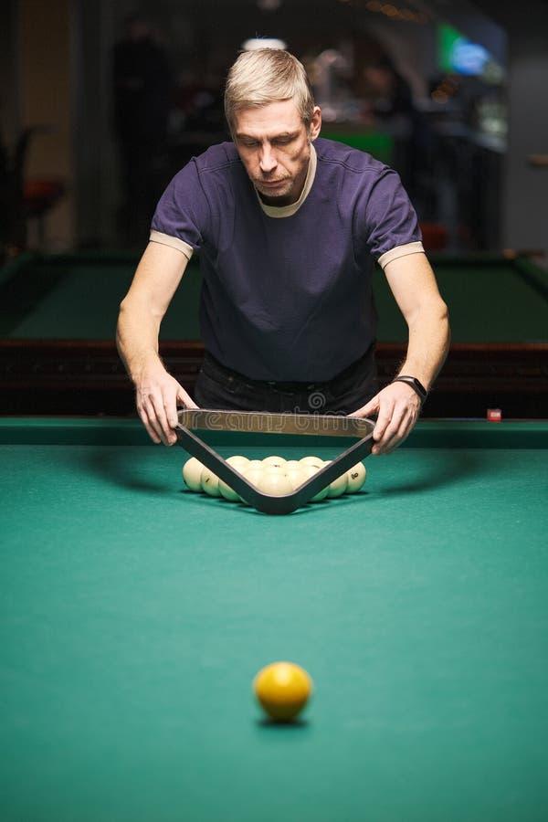 Der Spieler zielt auf den Ball im Billard stockfotografie