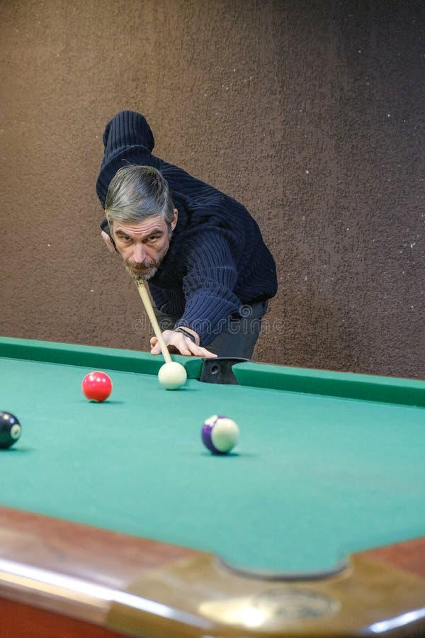 Der Spieler zielt auf den Ball im Billard lizenzfreies stockbild