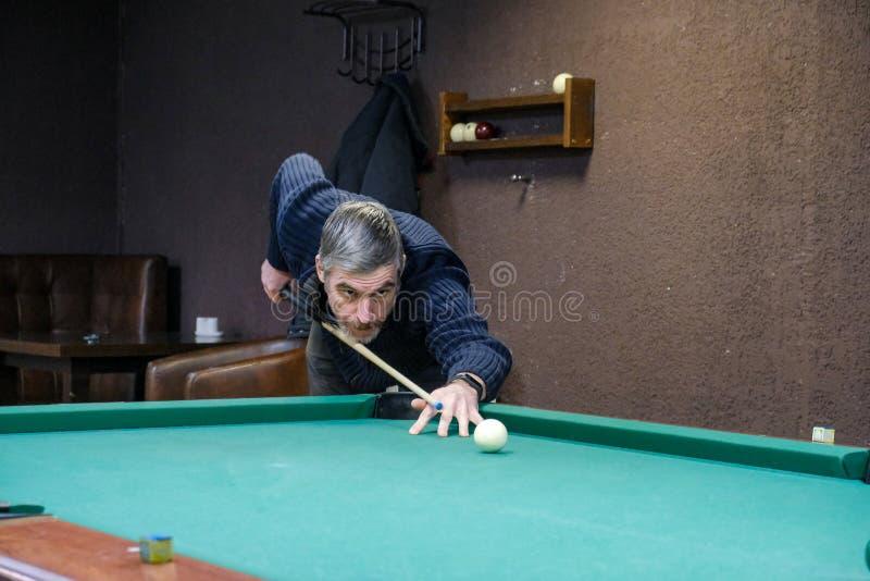 Der Spieler zielt auf den Ball im Billard stockfotos