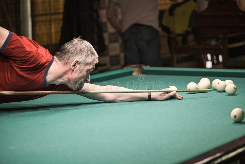 Der Spieler zielt auf den Ball im Billard stockfoto