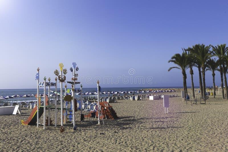 Der Spielplatz der bunte Kinder in der Seeart auf dem Strand durch das Meer an einem heißen Tag stockbild