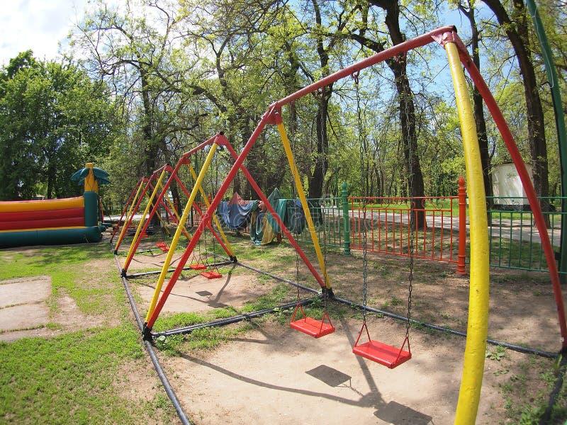 Der Spielplatz der Kinder mit Schwingen im Park lizenzfreie stockbilder