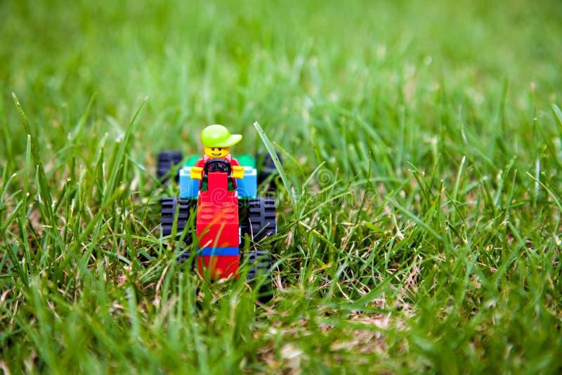 Der Spielzeug lego Traktor mit lego Fahrer lizenzfreie stockfotos