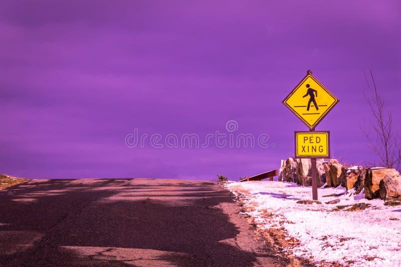 An der Spitze des Hügels, eines Fußgängerübergangzeichens und des sonderbaren purpurroten Himmels - was ist auf der anderen Seite stockfoto