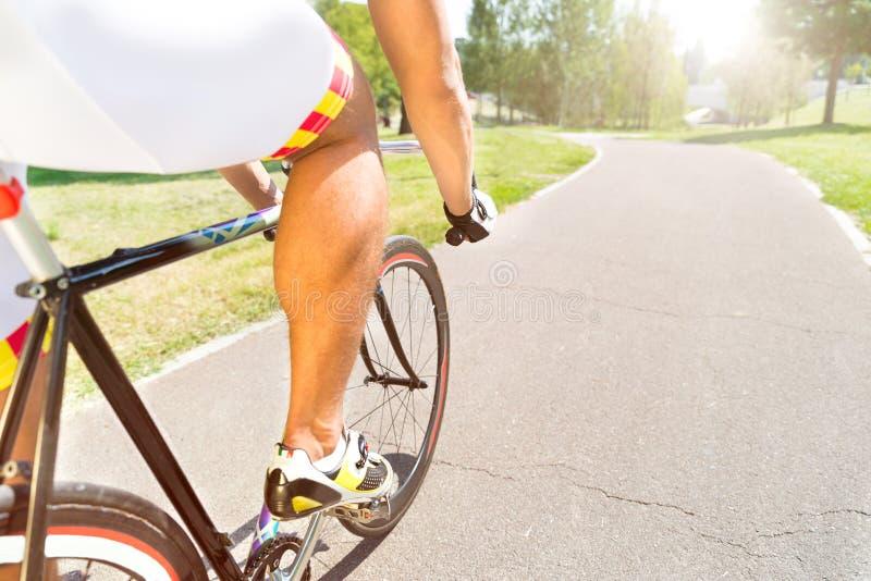 Der Sport der Männer, der Fahrrad im Park an der Asphaltstraße fährt stockfoto