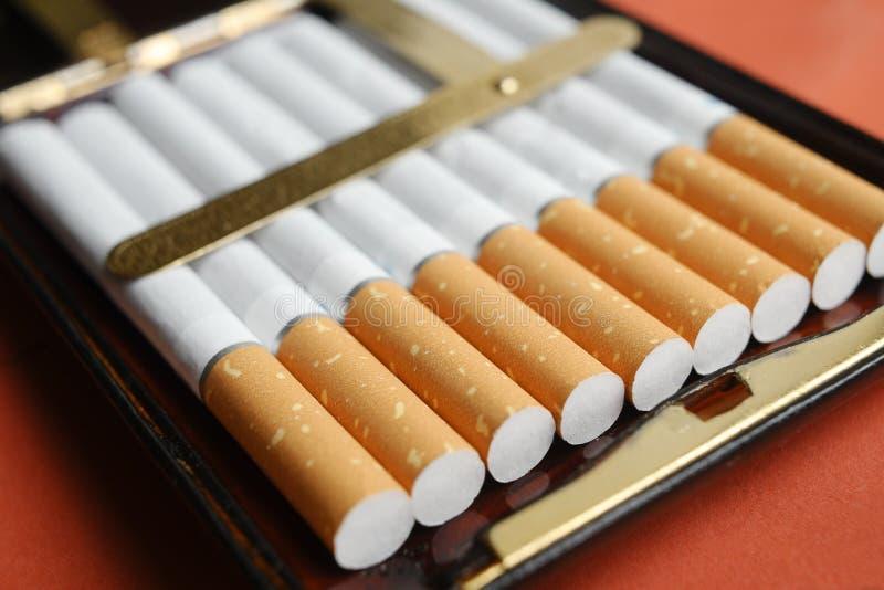 Der Stapel von Zigaretten in einem Weinlesekasten stockbild