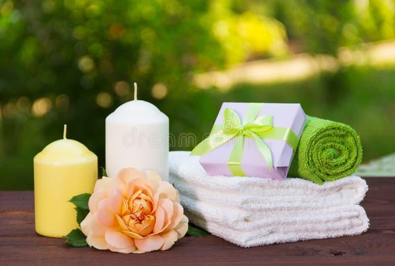 Der Stapel weiche Tücher, wohlriechend stieg, eine Kerze und ein Kästchen mit einem Geschenk Seifen-, Tuch- und Blumenschneeglöck lizenzfreie stockfotografie
