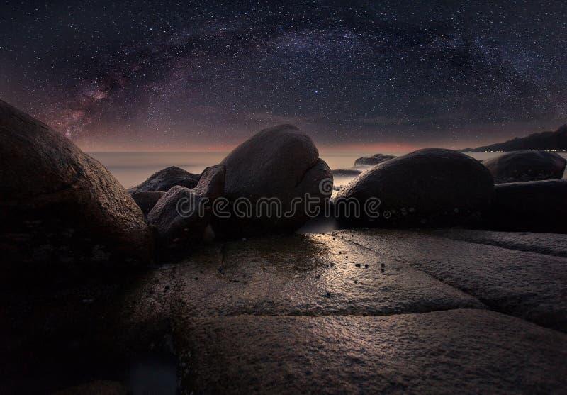 Der Steinstrand unter sternenklarer Nacht offenbar mit Milchstraße stockfotografie