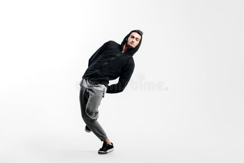 Der stilvolle junge Mann, der ein schwarzes Sweatshirt und grauen Hosen tr?gt, tanzt Stra?ent?nze auf einem wei?en Hintergrund stockbilder