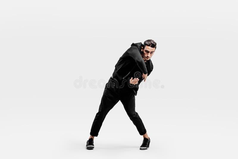 Der stilvolle junge Mann, der ein schwarzes Sweatshirt und schwarzen Hosen trägt, macht stilisierte Bewegungen von der Hüfte-poh stockfotos