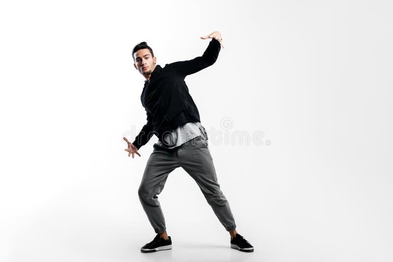 Der stilvolle junge Tänzer, der ein schwarzes Sweatshirt und grauen Hosen trägt, tanzt Hüfte-poh auf einem weißen Hintergrund stockfotos