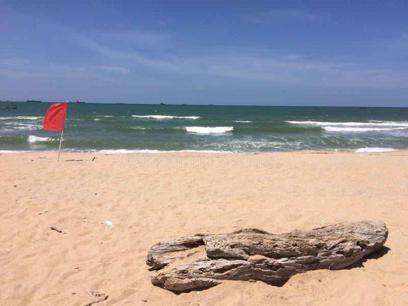 Der Strand der roten Fahne, der gestickt wird, um den Touristen zu erinnern, sollte Wasser nicht spielen stockfotografie