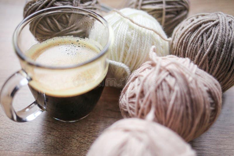 Der Stricknadeln, Beige und weißen Garn des Kaffees, sind auf dem Tisch lizenzfreies stockfoto