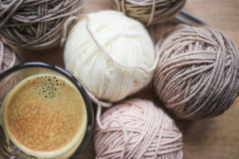 Der Stricknadeln, Beige und weißen Garn des Kaffees, sind auf dem Tisch stockfoto
