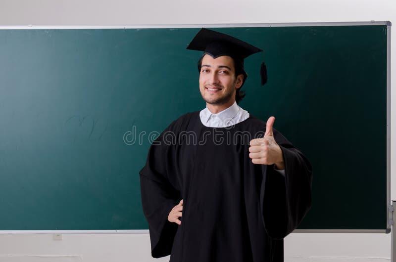 Der Student im Aufbaustudium vor gr?nem Brett stockfotografie